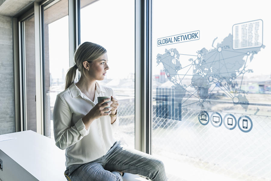 Young businesswoman looking at virtual world map at window pane in office Photograph by Westend61