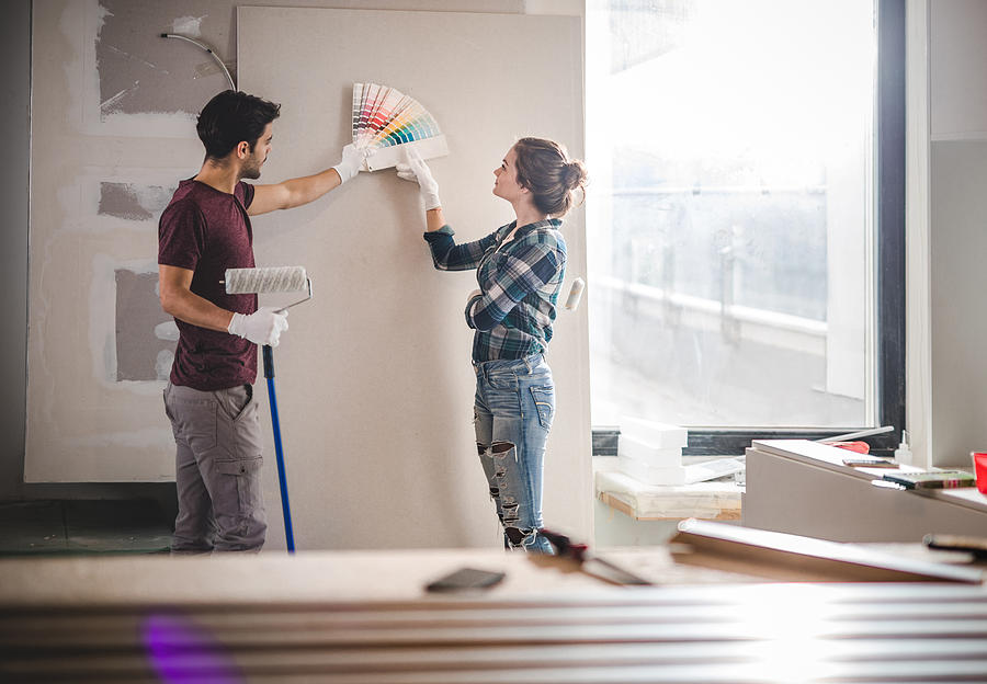 Young couple choosing the right color for their wall while renovating apartment. Photograph by Skynesher