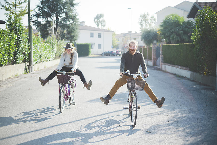 Young Couple Cycling With Legs Out Photograph by Eugenio Marongiu