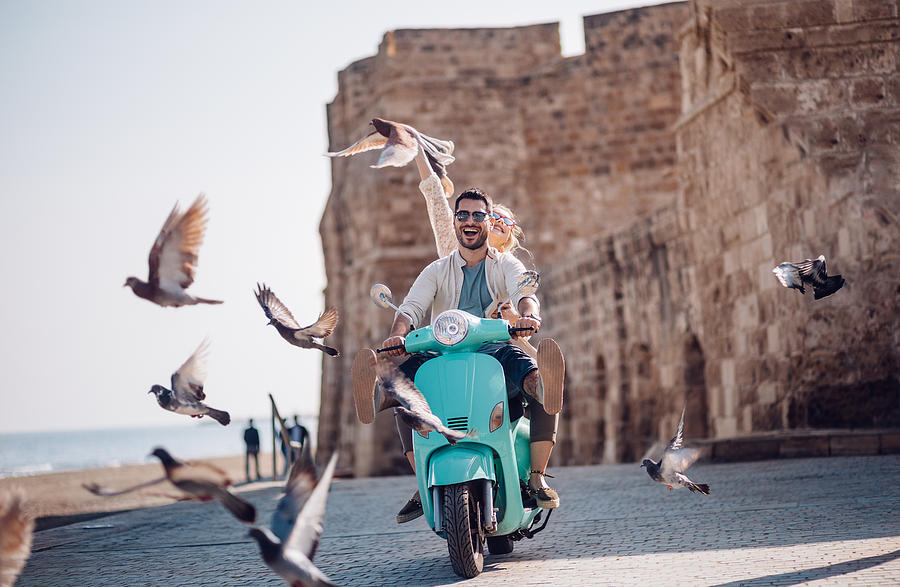Young couple having fun riding scooter in old European town Photograph by Wundervisuals