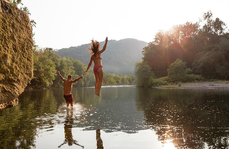 Young Couple Jumping Into River Photograph by Zave Smith