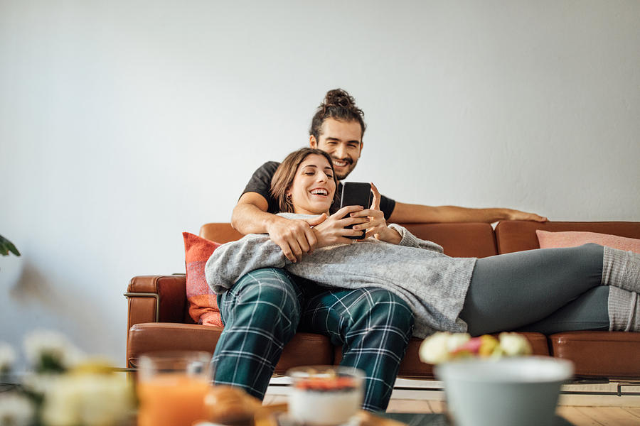 Young Couple With Smart Phone Relaxing On Sofa Photograph by Luis Alvarez