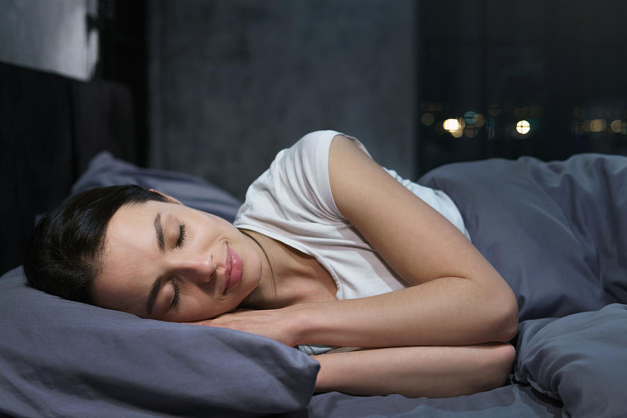 Young female sleeping peacefully in her bedroom at night, relaxing Photograph by Damir Khabirov