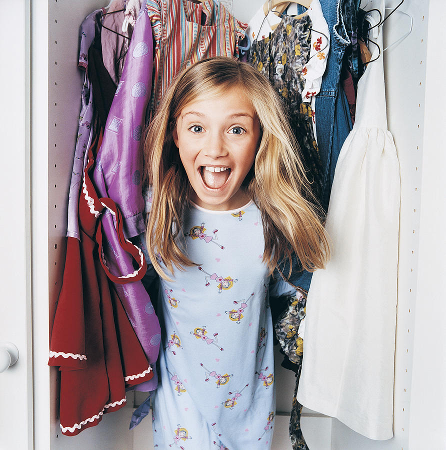 Young Girl Jumping out of a Wardrobe Photograph by Digital Vision.