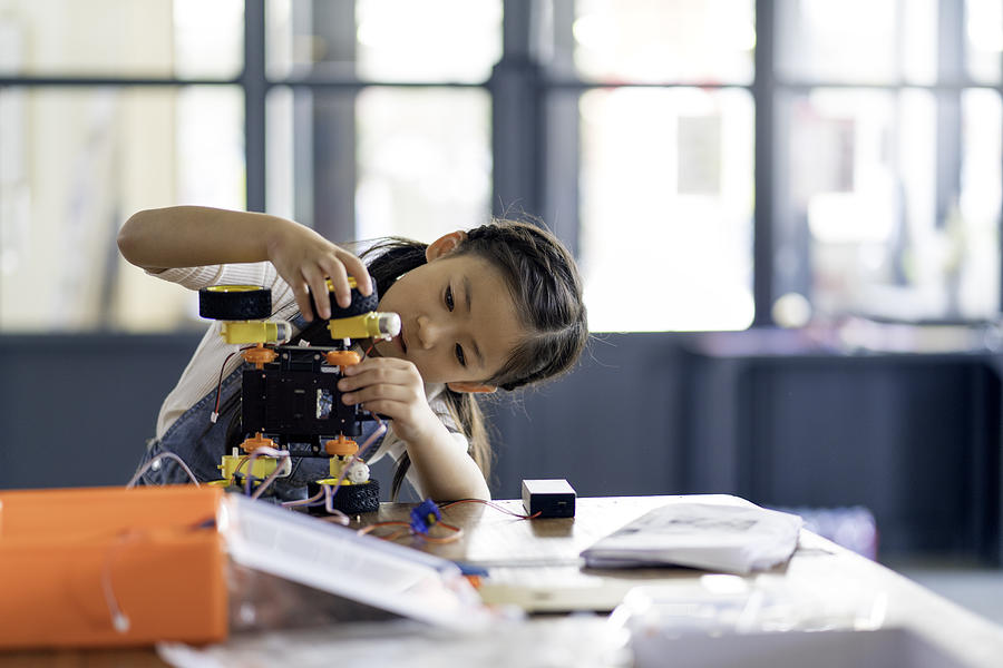 Young girl working on a robot design Photograph by JGalione