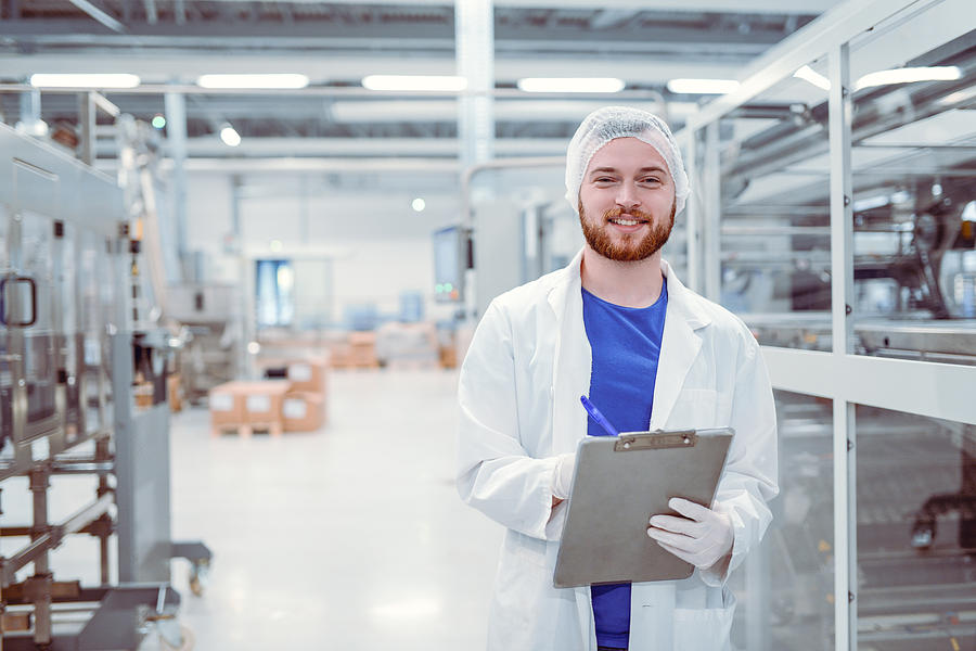 Young Handsome Smiling Scientist With Clipboard Posing in Factory Photograph by AleksandarGeorgiev