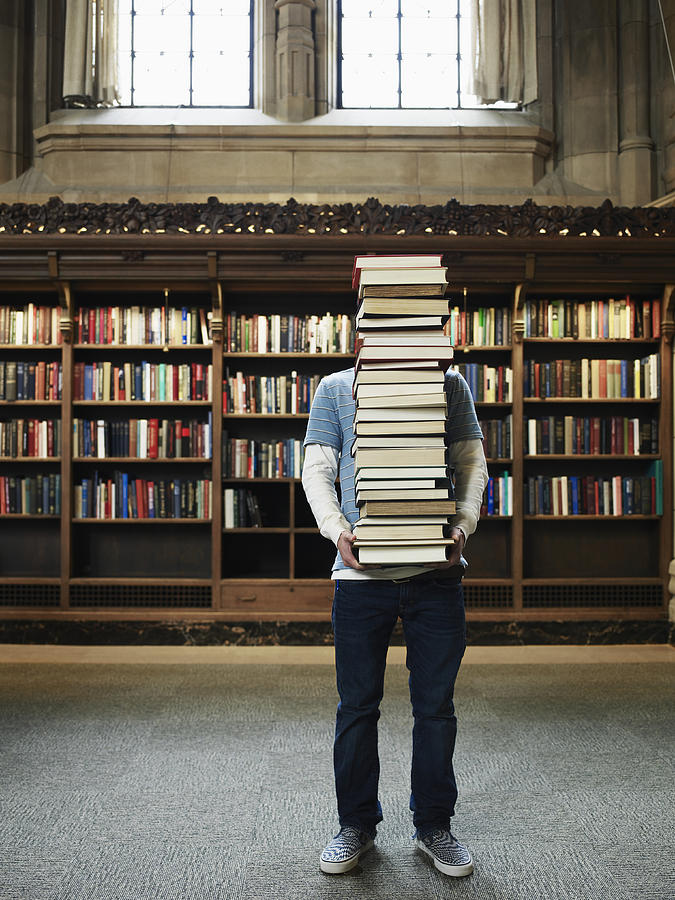 Young man carrying stack of books in university library Photograph by Thomas Barwick
