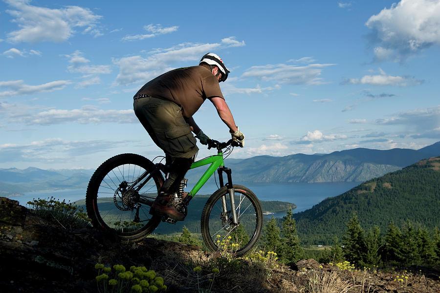 20s Photograph - Young Man Mountain Biking With Lake by Patrick Orton