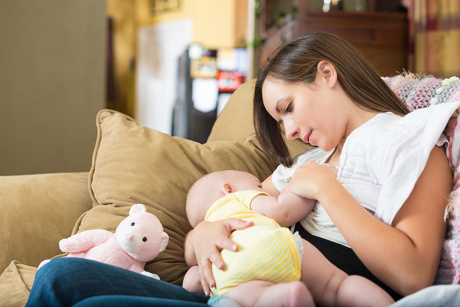 Young Mom Breastfeeding Infant Daughter At Home Photograph by Steve Debenport