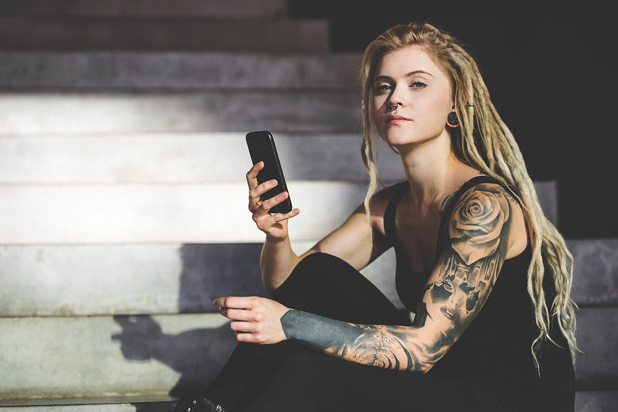 Young Tattooed Woman Texting Message On Mobile Phone Photograph by Nikada