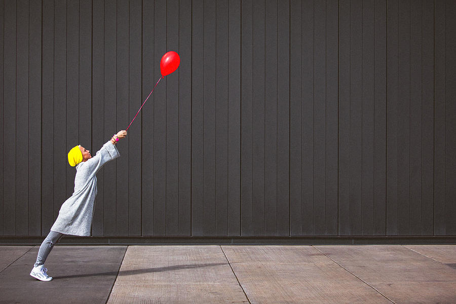 Young woman dancing and holding red balloon against the grey wall Photograph by Gruizza