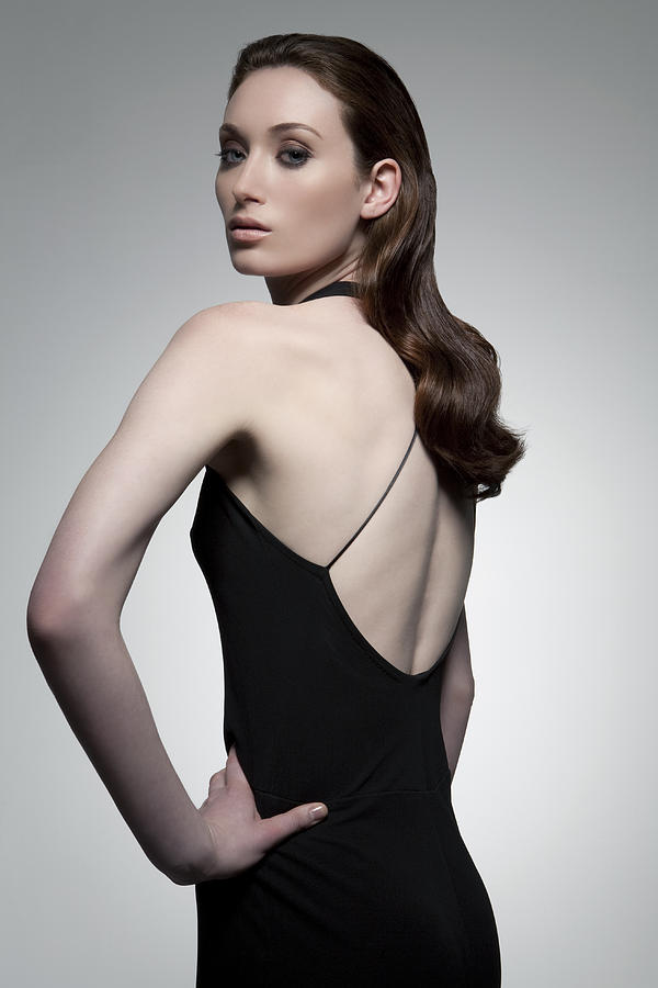 Young woman in black dress, portrait. Photograph by Andreas Kuehn