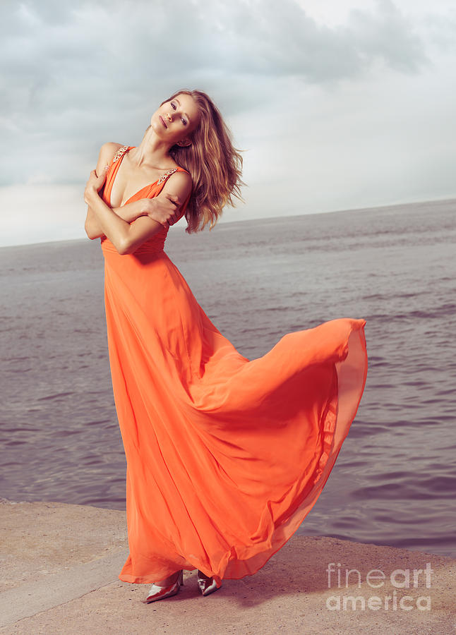 Woman Photograph - Young Woman In Orange Dress Flying In The Wind At Sea Shore by Oleksiy Maksymenko