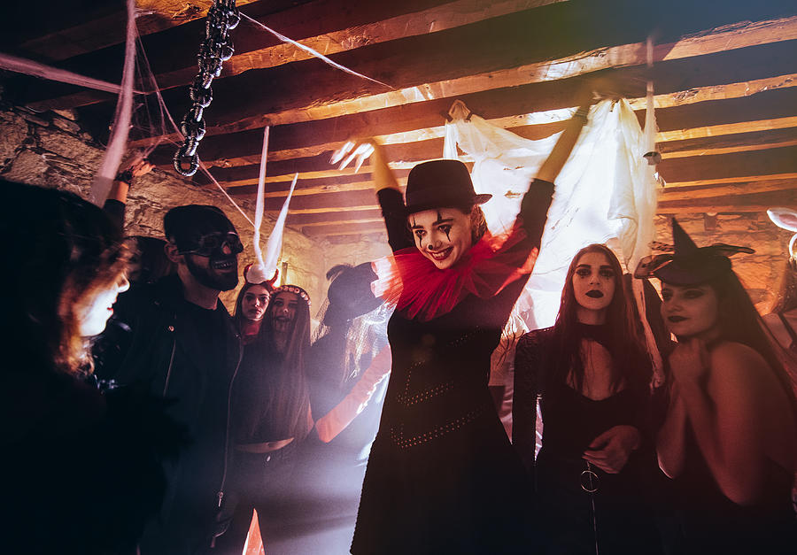Young Woman In Scary Clown Costume Dancing At Halloween Party Photograph by Wundervisuals