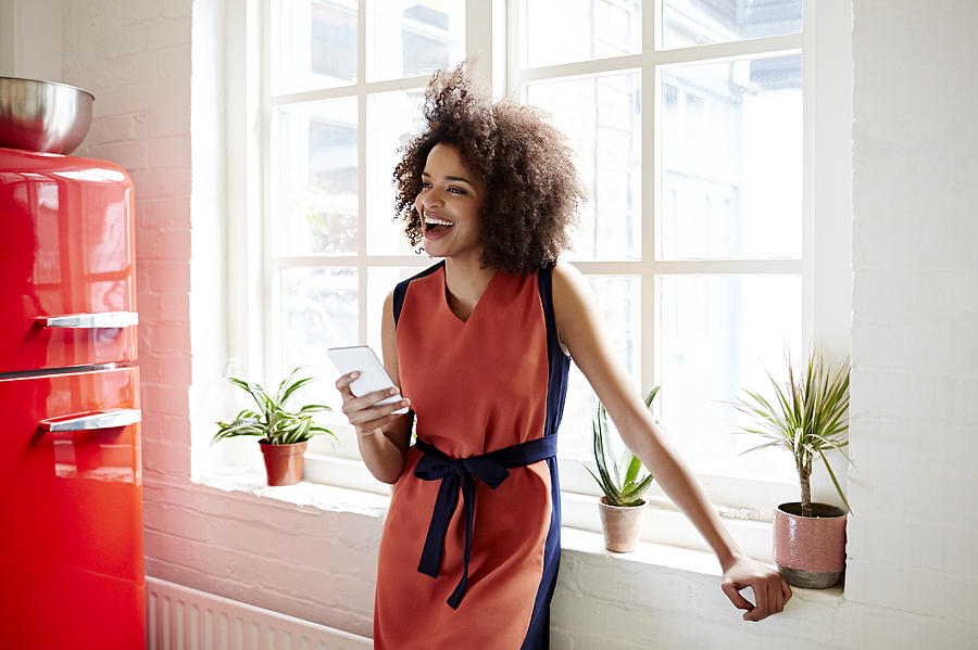Young Woman Laughing In A Trendy Apartment Photograph by Ezra Bailey