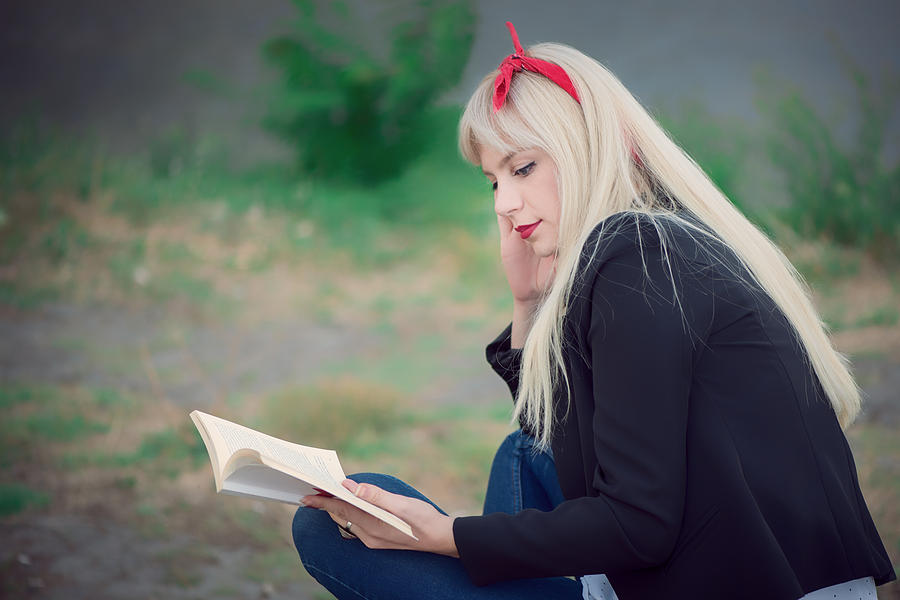 Young woman relaxing while reading a book at the park Photograph by Emilija Manevska