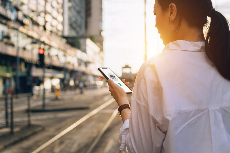 Young woman using mobile app on smartphone to arrange transportation ride in city street at sunset Photograph by D3sign