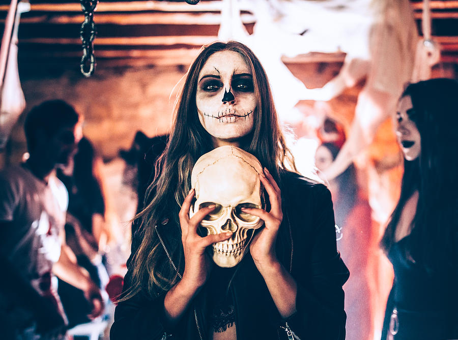 Young woman with skeleton make-up holding skull at Halloween party Photograph by Wundervisuals