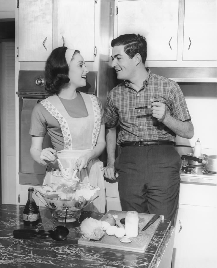 30-34 Years Photograph - Couple Standing In Kitchen, Smiling, (b&w) by George Marks
