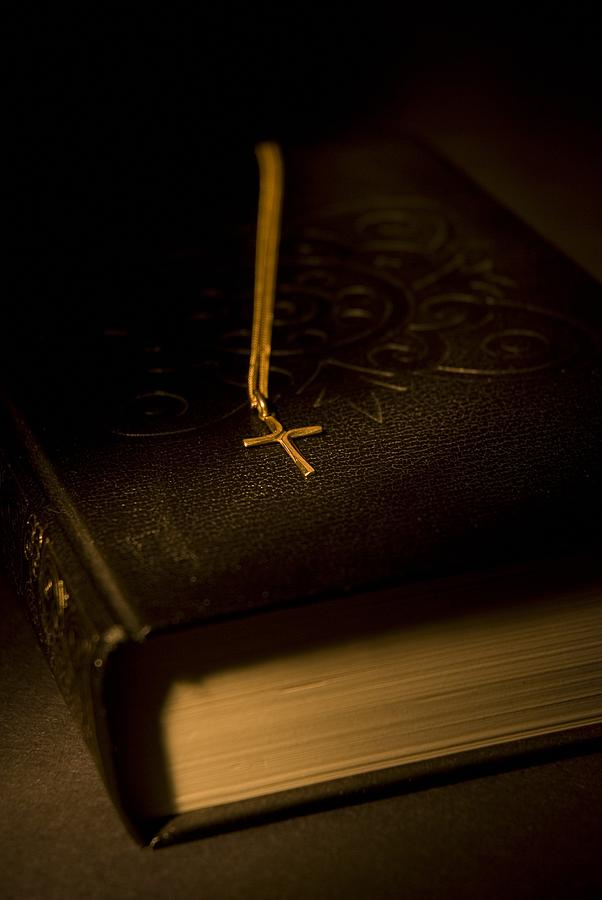 Bibles Photograph - Gold Cross Pendant Resting On A Book by Philippe Widling