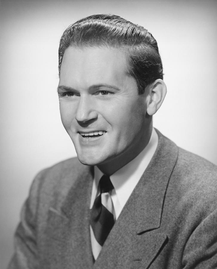 Adult Photograph - Smiling Man In Studio, (b&w), Portrait by George Marks