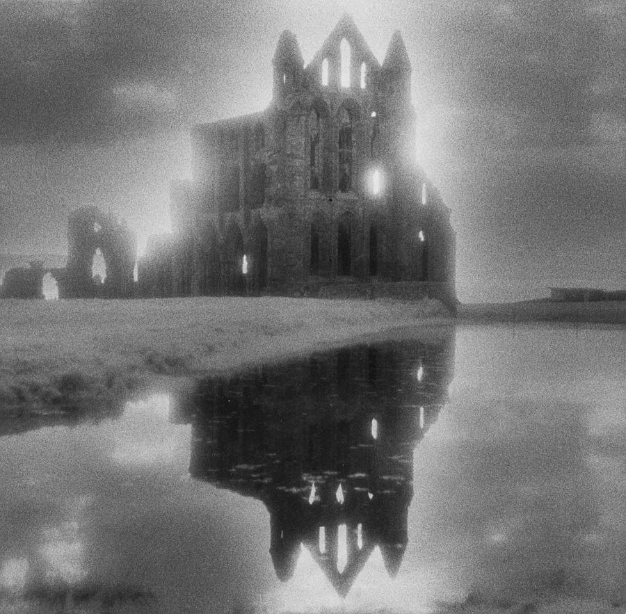 Eerie; Atmospheric; Spooky; Haunted; Haunting; Dramatic; Striking; Misty; Hazy; Lake; Reflection; English; Architecture; Exterior; Ruin; Ruins Photograph - Whitby Abbey by Simon Marsden