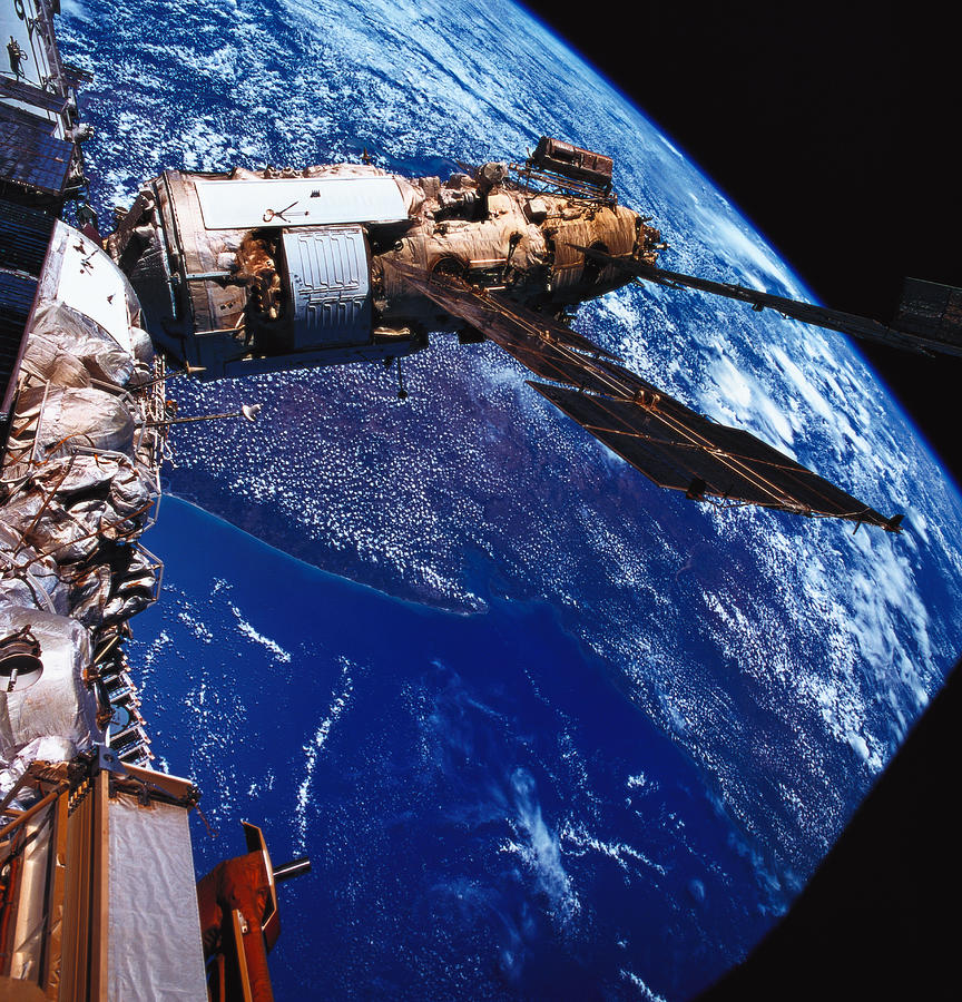 Square Photograph - A Satellite Orbiting Above The Earth by Stockbyte