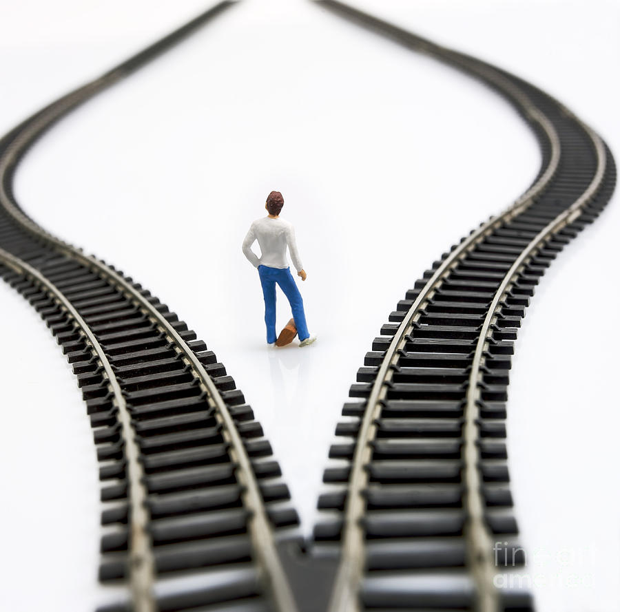 Ponder Photograph - Figurine Between Two Tracks Leading Into Different Directions Symbolic Image For Making Decisions. by Bernard Jaubert