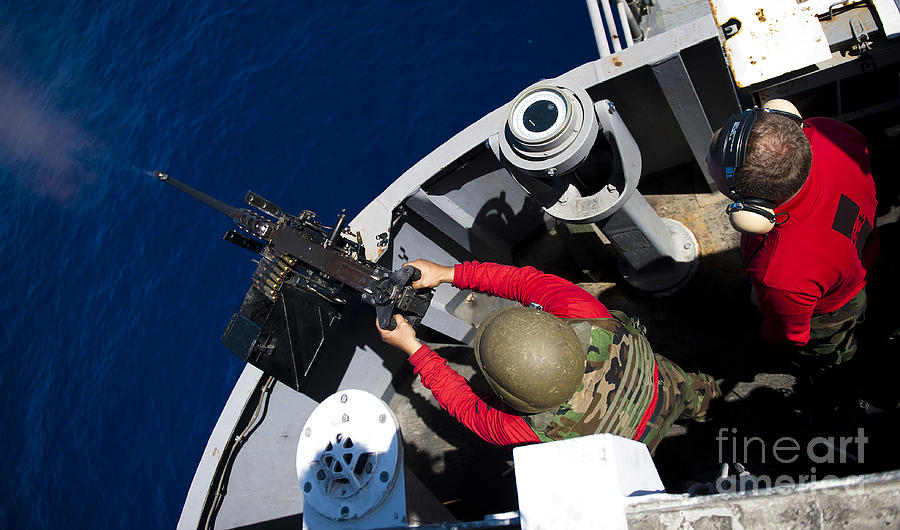Shooting Photograph - A Sailor Fires A .50-caliber Machine by Stocktrek Images