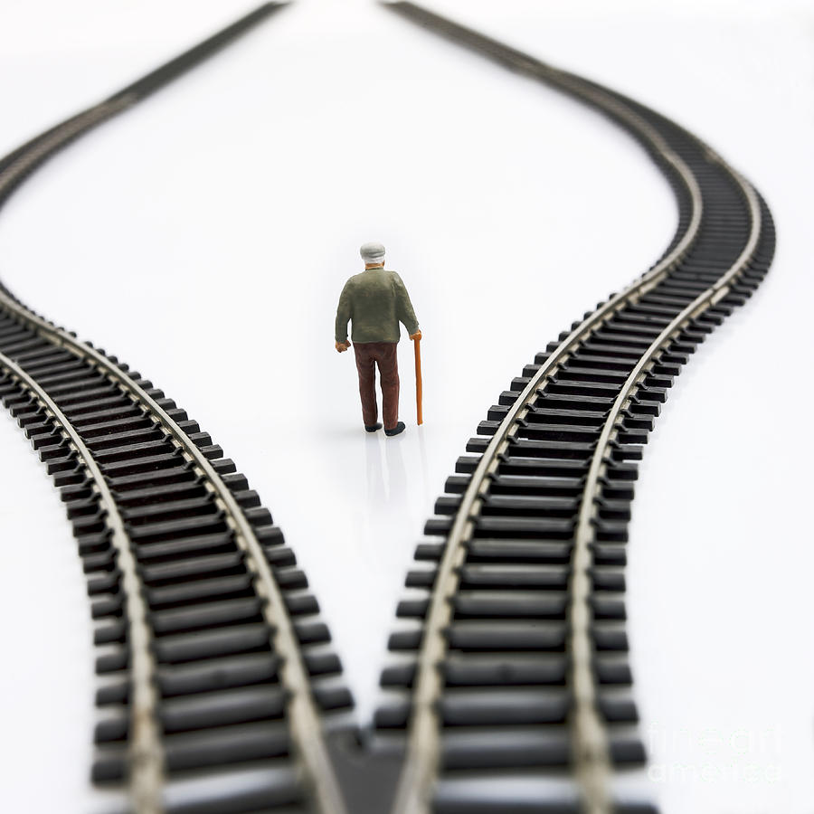 Stick Photograph - Figurine Between Two Tracks Leading Into Different Directions Symbolic Image For Making Decisions. by Bernard Jaubert