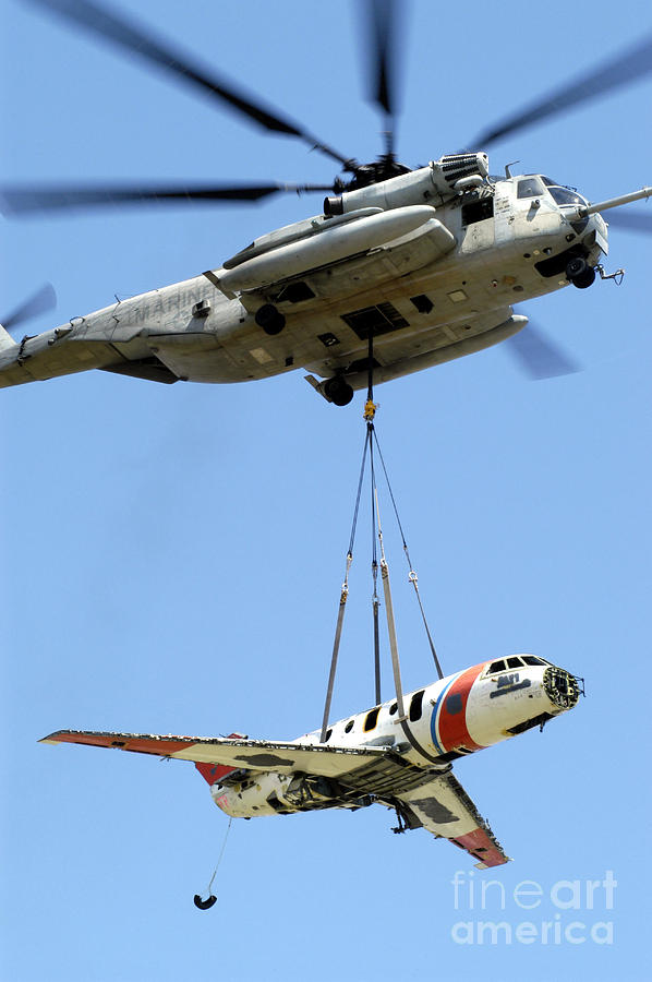 Aircraft Photograph - A Ch-53 Sea Stallion Lifts A Hu-25 by Stocktrek Images
