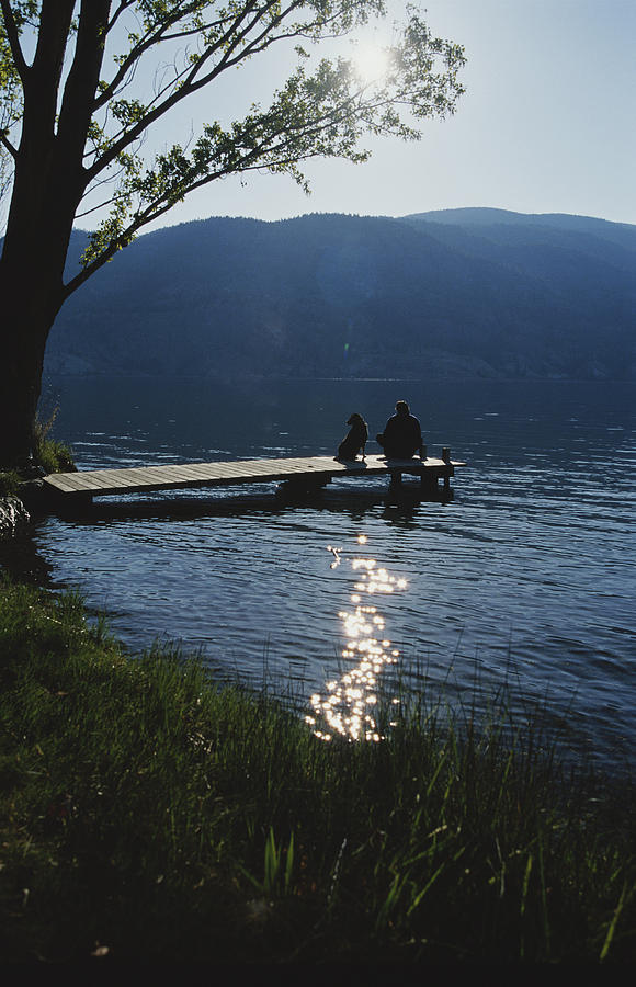 North America Photograph - A Man And His Dog On A Lake Skaha Dock by Mark Cosslett