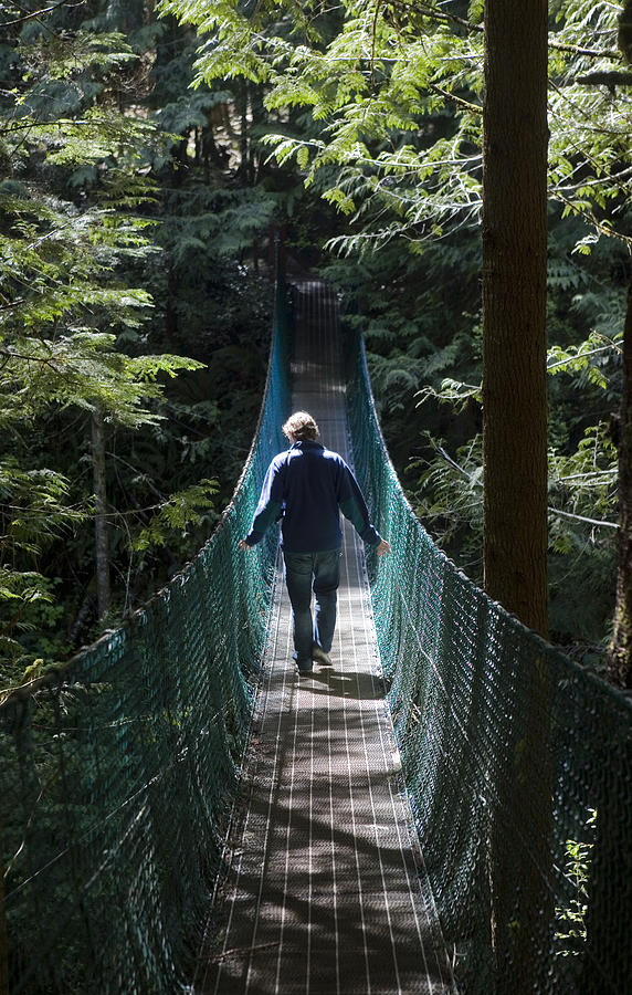 Daytime Photograph - A Man Walks Across A Suspension Bridge by Taylor S. Kennedy