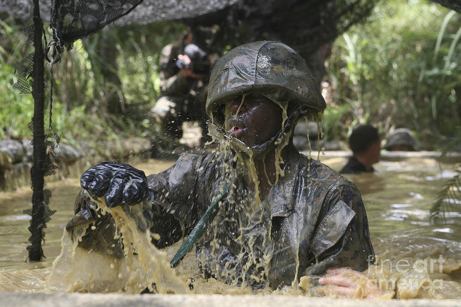 Obstacle Course Photograph - A Marine Splashes As He Makes His Way by Stocktrek Images
