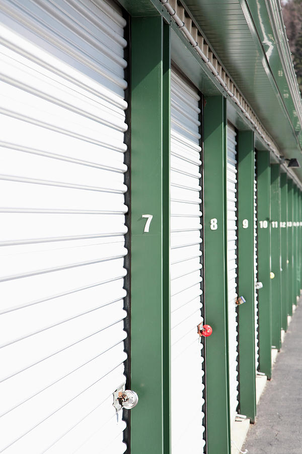 Vertical Photograph - A Row Of Locked Storage Units At A Self Storage Facility by Frederick Bass