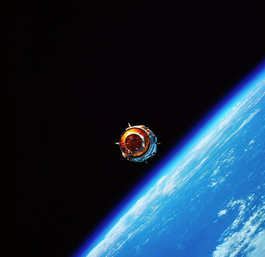 Horizontal Photograph - A Satellite In Orbit Above Earth by Stockbyte