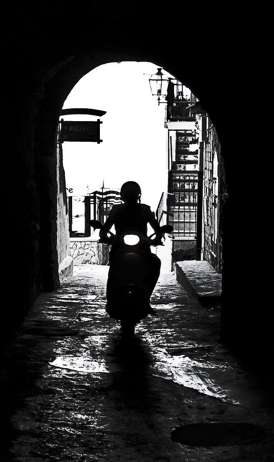 Lane Photograph - a scooter rider in the back light in a narrow street in Italy by Joana Kruse