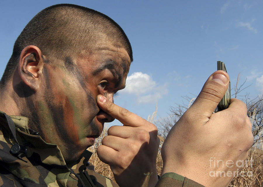 Disguise Photograph - A Soldier Applying Face Paint Prior by Stocktrek Images