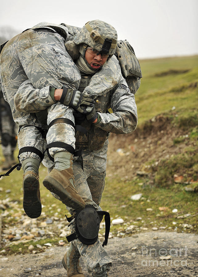 Military Photograph - A Soldier Transports A Fellow Wounded by Stocktrek Images