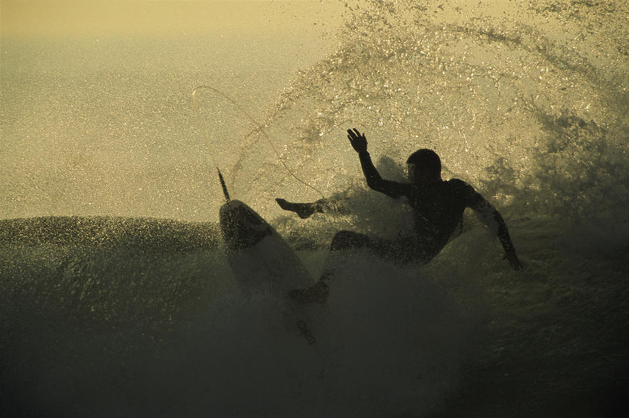 Silhouettes Photograph - A Surfer Wipes Out On A Breaking Wave by Tim Laman