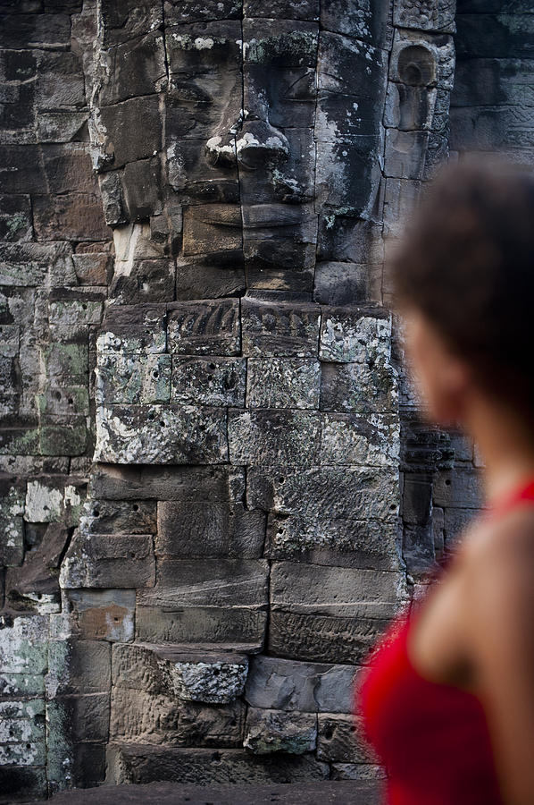 Cambodia Photograph - A Tourist Gazes At One Of The Enigmatic by Alex Treadway