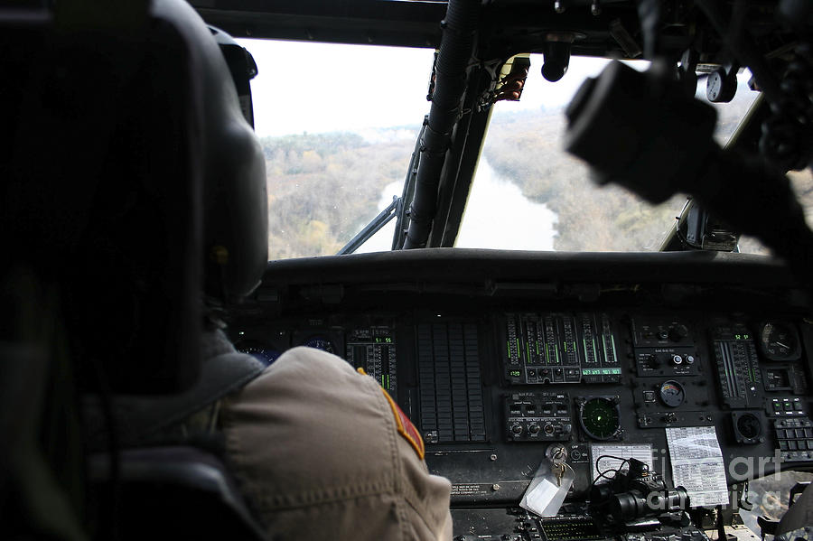 Cockpit Photograph - A Uh-60 Blackhawk Flies The River To An by Terry Moore
