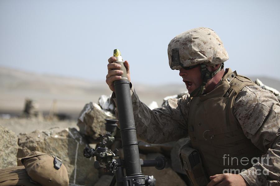Helmet Photograph - A U.s. Marine Loads A Mortar by Stocktrek Images