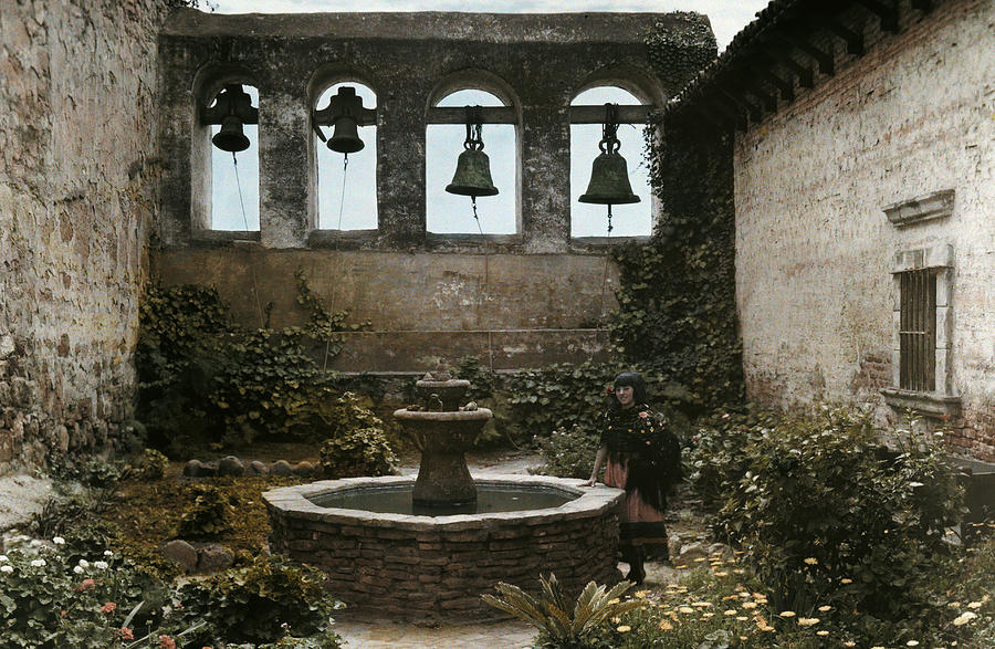 Day Photograph - A Woman Stands Next To A Fountain by Charles Martin