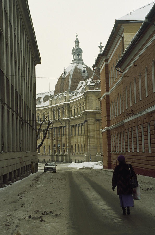 Brasov Photograph - A Woman Walks Down A Snowy  Street by Gordon Wiltsie