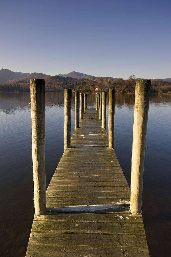Color Photograph - A Wooden Dock Going Into The Lake by John Short