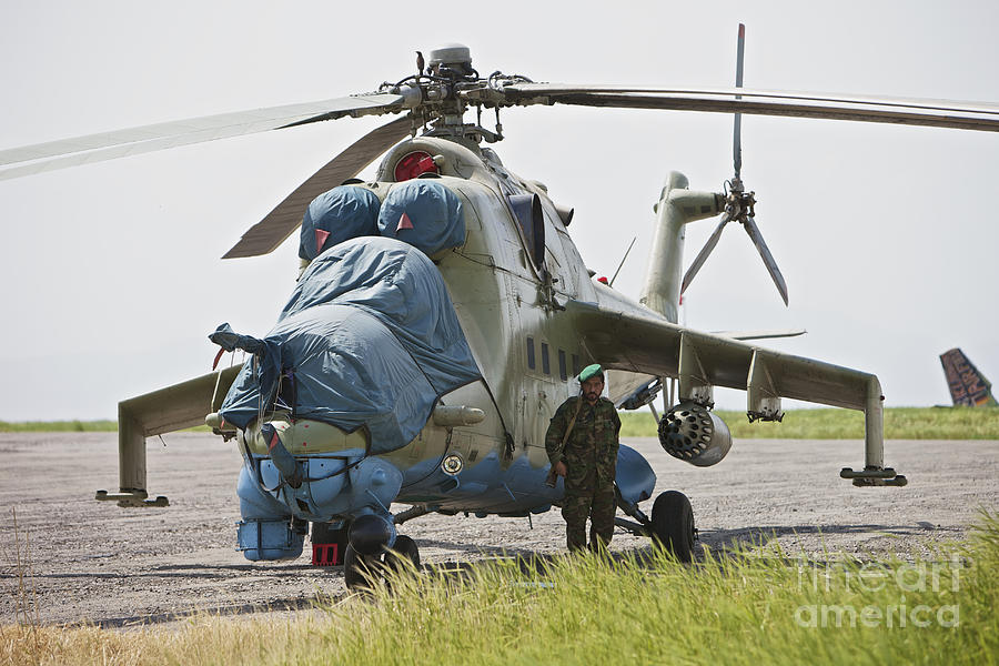 Airfield Photograph - An Afghan Army Soldier Guards A Mi-35 by Terry Moore