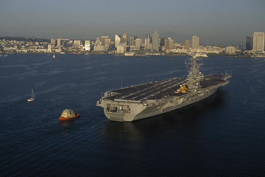Outdoors Photograph - An Aircraft Carrier With The Skyline by Phil Schermeister