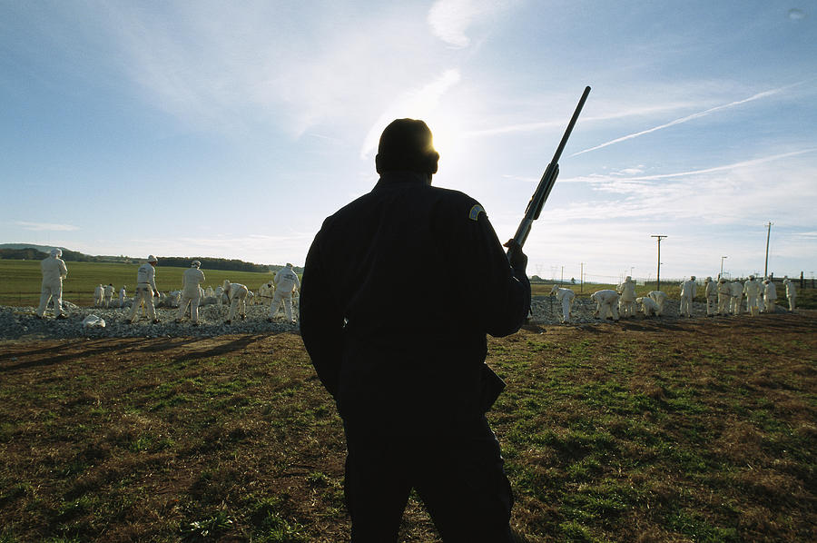 Peoples Photograph - An Armed Guard Watches Over Inmates by Bill Curtsinger