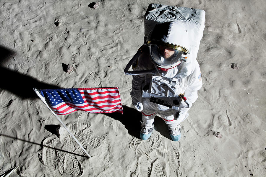 Adult Photograph - An Astronaut On The Surface Of The Moon Next To An American Flag by Caspar Benson